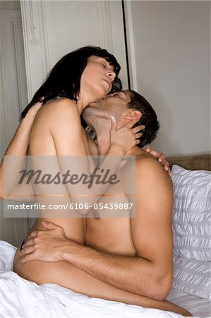 Young couple on bed, woman on top of man Stock Photo - Premium Royalty-Free, Image code: 6106-05439887