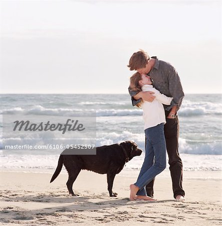 Girl (10-12) embracing father on beach next to black labrador Stock Photo - Premium Royalty-Free, Image code: 6106-05452507