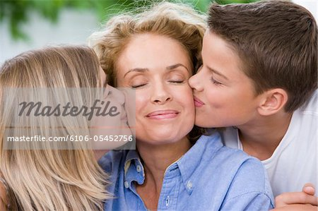 Mother being kissed by son and daughter (13-15) eyes closed, smiling Stock Photo - Premium Royalty-Free, Image code: 6106-05452756