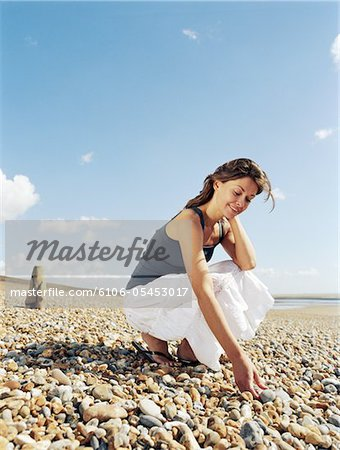 Young woman crouching on pebble beach, picking up pebbles, smiling Stock Photo - Premium Royalty-Free, Image code: 6106-05453017