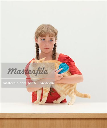 Girl (9-11) with arms around cat standing on table Stock Photo - Premium Royalty-Free, Image code: 6106-05456584