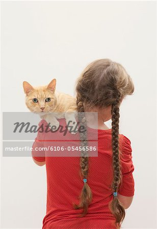 Girl (9-11) holding cat, cat looking over shoulder Stock Photo - Premium Royalty-Free, Image code: 6106-05456586