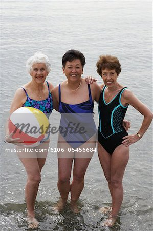 Three senior women wading in sea, smiling, portrait Stock Photo - Premium Royalty-Free, Image code: 6106-05456684