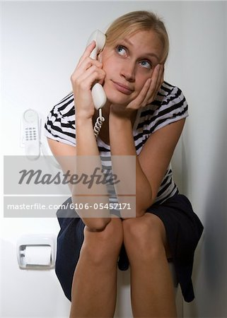 Woman sitting on toilet, using telephone Stock Photo - Premium Royalty-Free, Image code: 6106-05457171