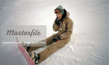 Teenage female snowboarder (17-19) sitting on snow, licking snowball Stock Photo - Premium Royalty-Free, Image code: 6106-05457464