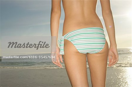 Teenage girl (16-18) wearing bikini, at beach, mid section, rear view Stock Photo - Premium Royalty-Free, Image code: 6106-05457634