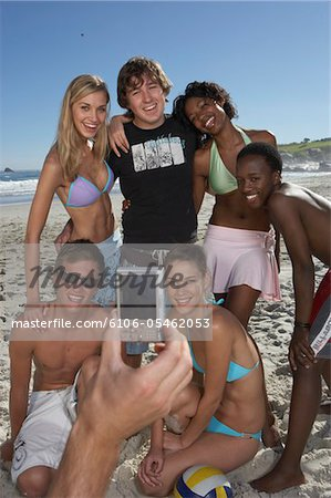 Group of young friends posing for photograph on beach, smiling Stock Photo - Premium Royalty-Free, Image code: 6106-05462053