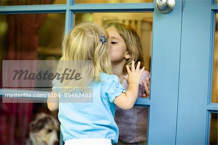 Two sisters (20 months-3) kissing each other through French door Stock Photo - Premium Royalty-Free, Image code: 6106-05462402