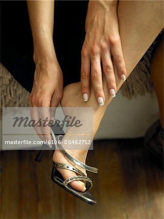 Woman putting on sandal, close-up on foot Stock Photo - Premium Royalty-Free, Image code: 6106-05462712