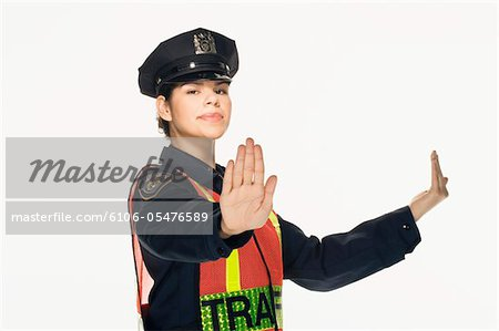 Traffic police officer directing traffic on white background, portrait Stock Photo - Premium Royalty-Free, Image code: 6106-05476589
