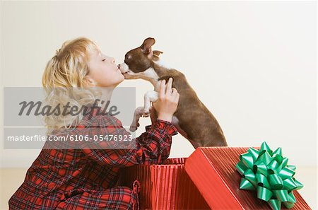 girl (6-8) kissing Boston Terrier puppy in giftwrapped box Stock Photo - Premium Royalty-Free, Image code: 6106-05476923