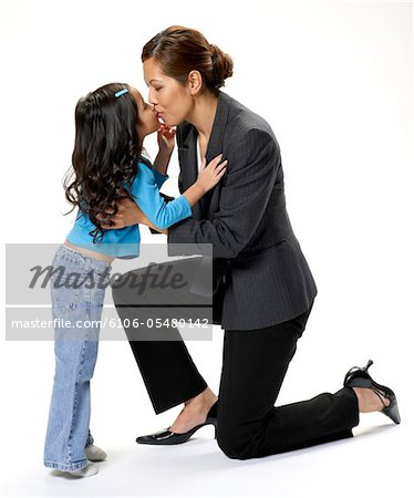 Mid adult businesswoman and girl (4-5) kissing, side view Stock Photo - Premium Royalty-Free, Image code: 6106-05480142