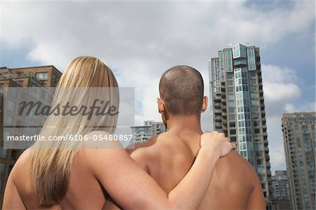 Naked young couple embracing against city buildings, rear view Stock Photo - Premium Royalty-Free, Image code: 6106-05480857