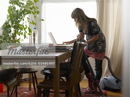 Woman standing by vacuum cleaner using laptop on dining table Stock Photo - Premium Royalty-Free, Image code: 6106-05480997