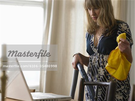 Young woman holding duster plant looking at laptop in living room Stock Photo - Premium Royalty-Free, Image code: 6106-05480998