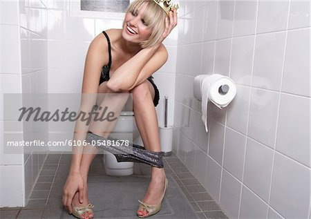 Young woman wearing crown sitting on toilet, laughing Stock Photo - Premium Royalty-Free, Image code: 6106-05481678
