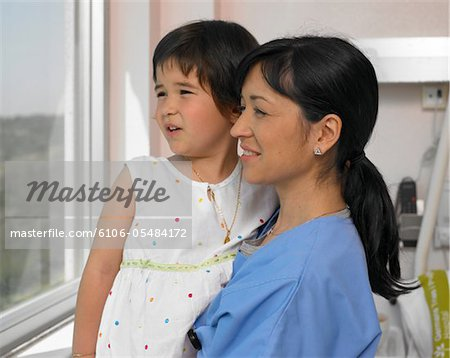 Doctor looking out of window with girl (5-7 years), side view Stock Photo - Premium Royalty-Free, Image code: 6106-05484172