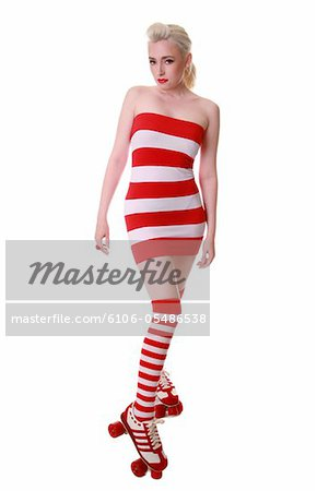Caucasian model wearing a red and white striped dress and socks with roller skates Stock Photo - Premium Royalty-Free, Image code: 6106-05486538