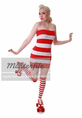 Caucasian model wearing a red and white striped dress and socks with roller skates Stock Photo - Premium Royalty-Free, Image code: 6106-05486551