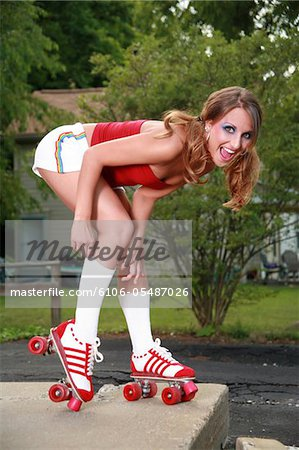 A beautiful model in roller skates pulling up her tube socks. Stock Photo - Premium Royalty-Free, Image code: 6106-05487026