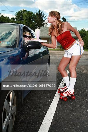 Roller waitress serving a milkshake and a hot dog to a customer. Stock Photo - Premium Royalty-Free, Image code: 6106-05487029
