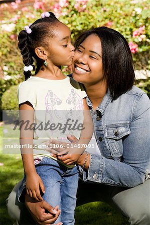 Photo of an African American mother and daughter - mother getting a kiss on the cheek. Stock Photo - Premium Royalty-Free, Image code: 6106-05487095