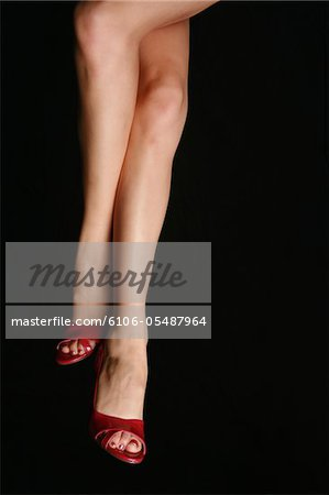 A pair of woman's legs isolated on black. Stock Photo - Premium Royalty-Free, Image code: 6106-05487964