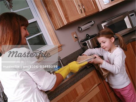 A daughter helping her mother with household chores. Stock Photo - Premium Royalty-Free, Image code: 6106-05488099