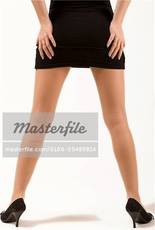 young slender woman in black minidress standing with her legs slightly spread hands on her behind Stock Photo - Premium Royalty-Free, Image code: 6106-05489814