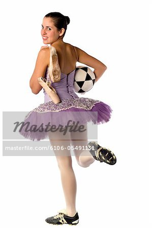 Image shows a ballerina and the contrast between the arts and sports: Ballet and Soccer Stock Photo - Premium Royalty-Free, Image code: 6106-05491131
