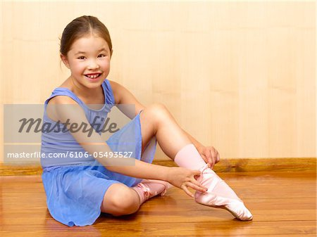 Child Ballerina tying ballet shoes Stock Photo - Premium Royalty-Free, Image code: 6106-05493527