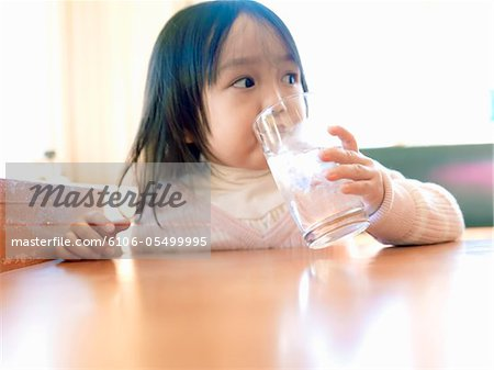 Girl who drinks water at a restaurant Stock Photo - Premium Royalty-Free, Image code: 6106-05499995