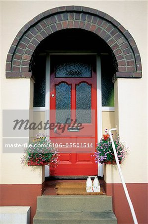 Bottles of milk and hanging plants outside house with red door in Totnes, England Stock Photo - Premium Royalty-Free, Image code: 6106-05501514