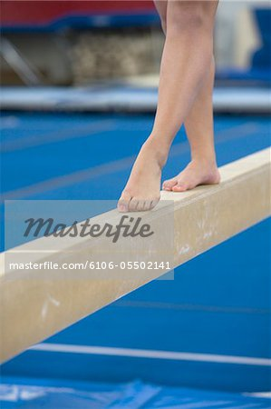 Teenage girl (16-17 years) on balance beam, low section Stock Photo - Premium Royalty-Free, Image code: 6106-05502141