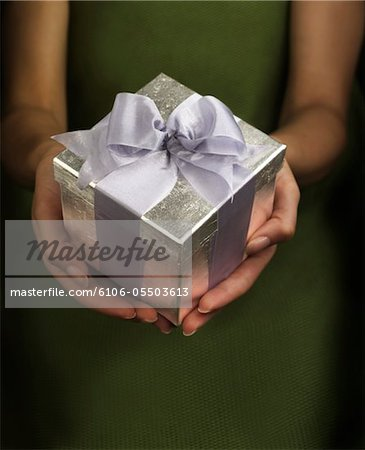 Woman holding gift in box, mid section, focus on gift Stock Photo - Premium Royalty-Free, Image code: 6106-05503613