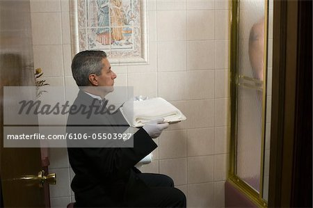 Butler waiting with towel while mature man is taking shower, side view Stock Photo - Premium Royalty-Free, Image code: 6106-05503927