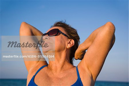 Senior woman stretching on beach, close-up Stock Photo - Premium Royalty-Free, Image code: 6106-05506164