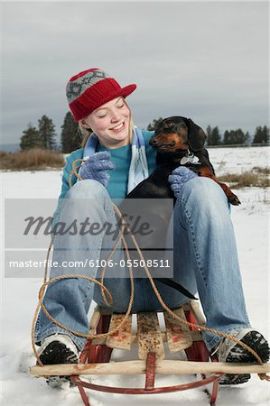 Young woman on sledge with dog Stock Photo - Premium Royalty-Free, Image code: 6106-05508511