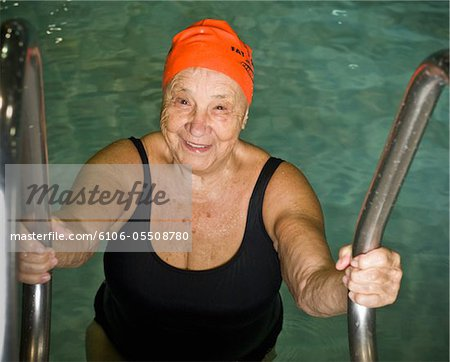 Elderly woman climbing out of swimming pool Stock Photo - Premium Royalty-Free, Image code: 6106-05508780