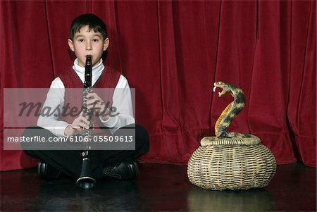 Boy (8-9) playing clarinet on stage charming snake Stock Photo - Premium Royalty-Free, Image code: 6106-05509613