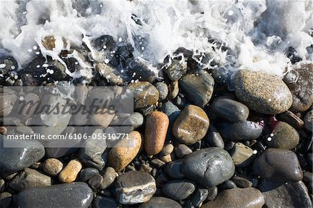 Surf splashes over stones on beach Stock Photo - Premium Royalty-Free, Image code: 6106-05510771