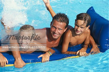 Father with boys (8-11) lying on pool raft in pool Stock Photo - Premium Royalty-Free, Image code: 6106-05528372
