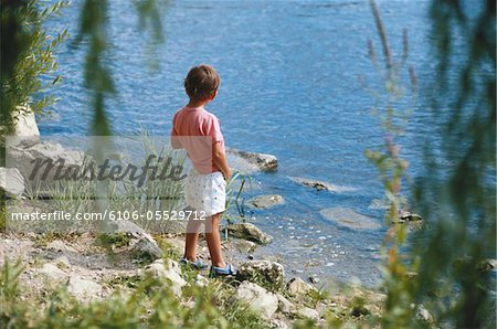 Boy (4-5) urinating by river, rear view Stock Photo - Premium Royalty-Free, Image code: 6106-05529712
