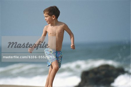 Boy (8-9) running on beach, looking over shoulder Stock Photo - Premium Royalty-Free, Image code: 6106-05529755