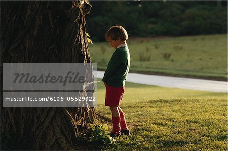 Boy (4-7) urinating on tree, side view Stock Photo - Premium Royalty-Free, Image code: 6106-05529922