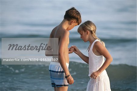 Boy and girl (6-11) standing on beach, looking at shell Stock Photo - Premium Royalty-Free, Image code: 6106-05530307