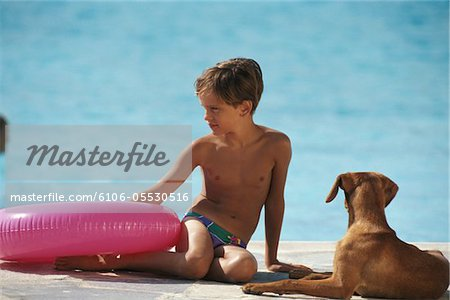 Boy (8-11) with dog holding rubber ring by poolside Stock Photo - Premium Royalty-Free, Image code: 6106-05530516