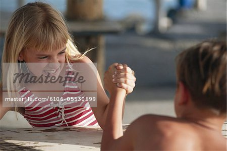 Boy and girl (6-11) arm wrestling Stock Photo - Premium Royalty-Free, Image code: 6106-05530599