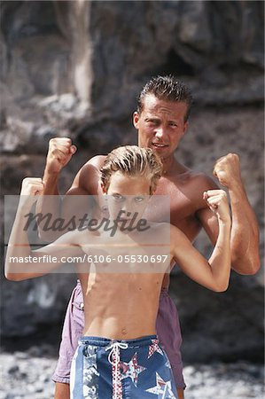 Man and boy (10-11) flexing muscles on beach Stock Photo - Premium Royalty-Free, Image code: 6106-05530697