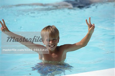 Boy (10-13) showing victory sign in swimming pool, elevated view Stock Photo - Premium Royalty-Free, Image code: 6106-05531415
